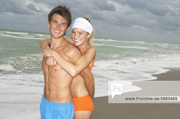 Pärchen am Strand umarmend