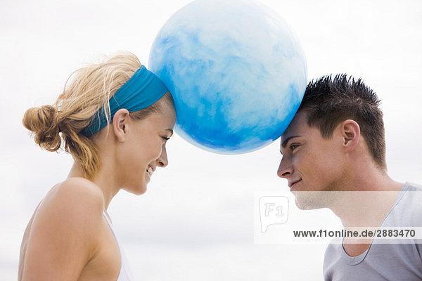 Paar balancierender Strandball zwischen ihren Köpfen