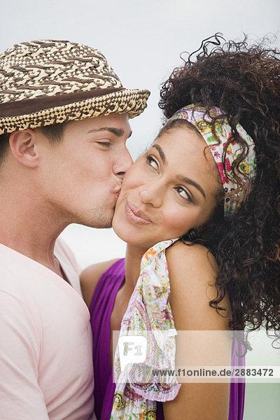 Mann küsst eine Frau auf die Wange