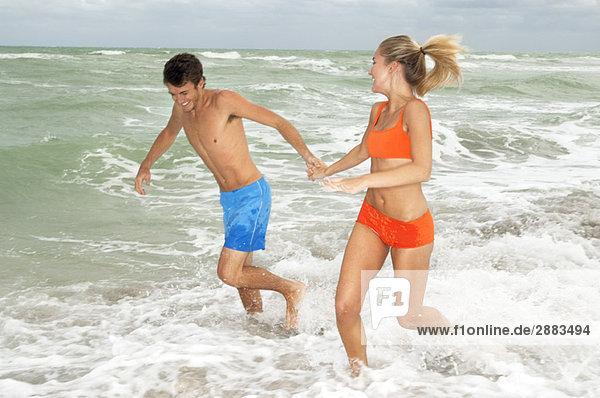 Paar läuft im Wasser am Strand.