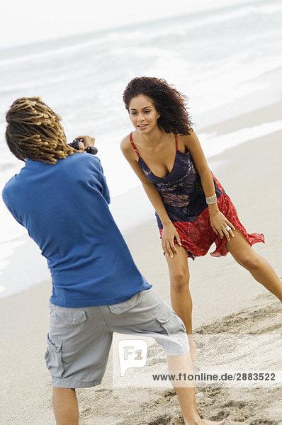 Mann macht ein Video von einer Frau am Strand