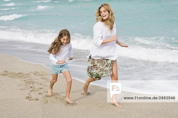 Frau läuft mit ihrer Tochter am Strand.