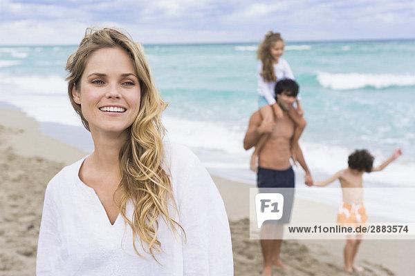 Frau lächelt mit ihrer Familie im Hintergrund