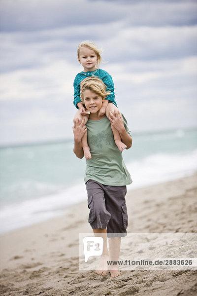 Junge  der seine Schwester auf den Schultern am Strand trägt.