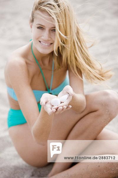 Frau mit Muscheln am Strand