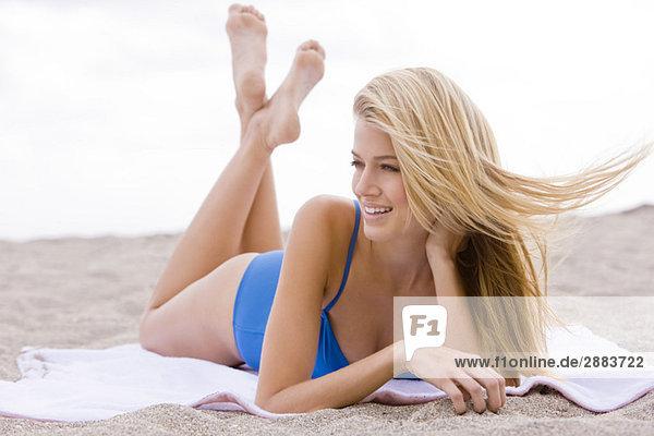 Frau beim Sonnenbaden am Strand