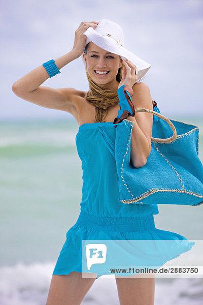 Frau mit einer Tasche am Strand