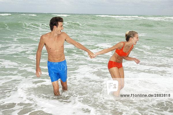 Paar hält sich an den Händen und geht im Wasser am Strand spazieren.