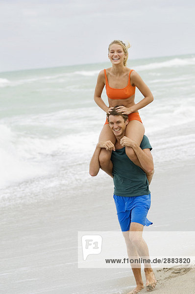 Mann  der eine Frau auf seinen Schultern am Strand trägt.