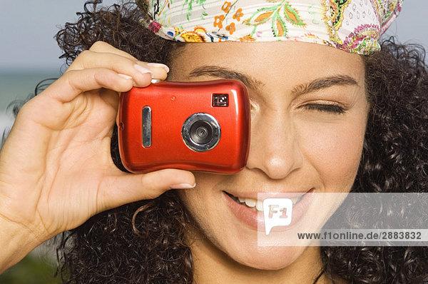 Nahaufnahme einer Frau  die mit einer Digitalkamera fotografiert.