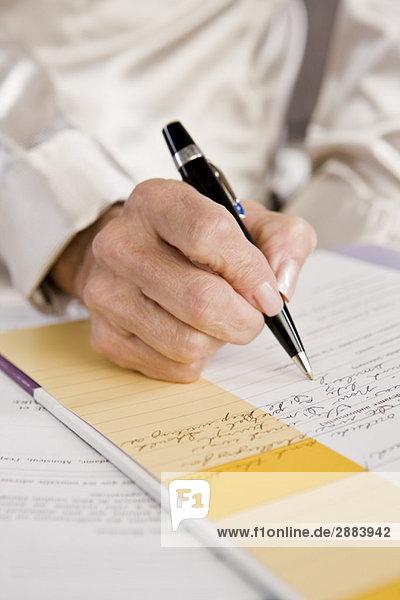 Mittelteilansicht einer Frau beim Ausfüllen eines Bewerbungsformulars