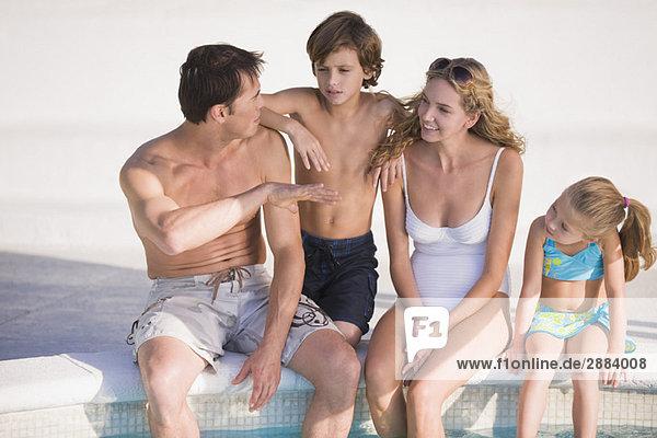 Familie am Pool sitzend und lächelnd