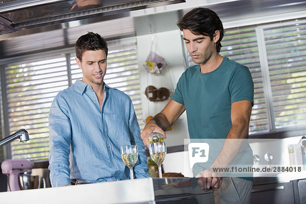 Ein Mann gießt Wein in Gläser für seinen Freund in der Küche.