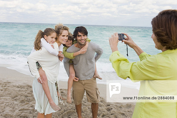 Frau beim Fotografieren ihrer Familie mit einer Digitalkamera