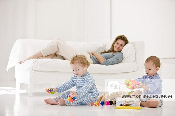 Babys  die mit Spielzeug spielen  und ihre Mutter  die auf einer Couch liegt