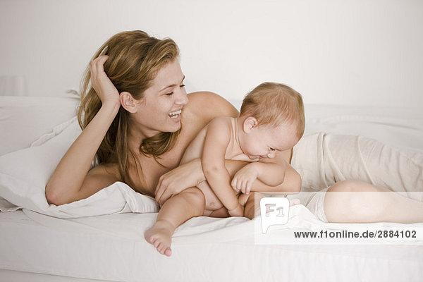 Frau spielt mit ihrer Tochter auf dem Bett