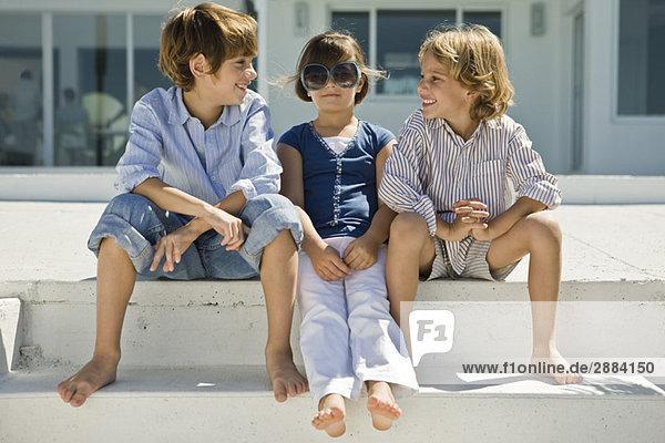 Drei Kinder sitzen zusammen