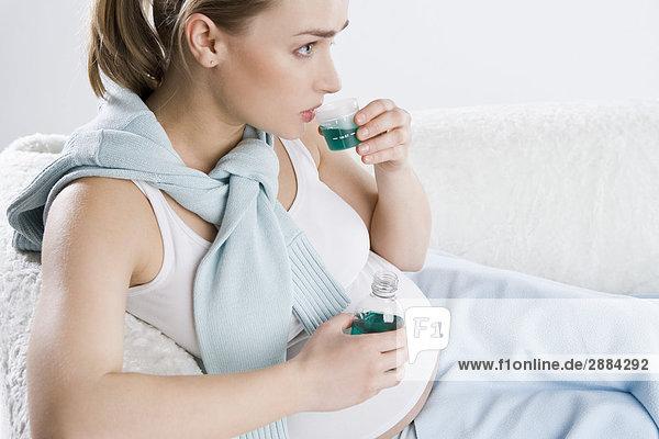 schwangere Frau trinkt Sirup