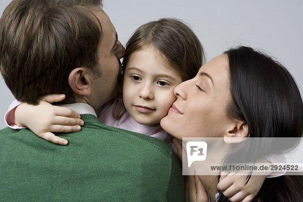 Eine Tochter  die ihre Eltern umarmt.