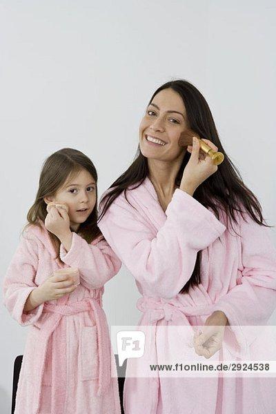 Mutter und Tochter in rosa Bademänteln mit Make-up