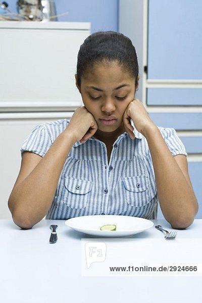 Eine junge Frau schaut auf eine Gurkenscheibe auf einem Teller hinunter