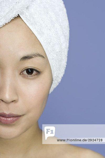 Porträt einer Frau mit einem Handtuch um die Haare gewickelt