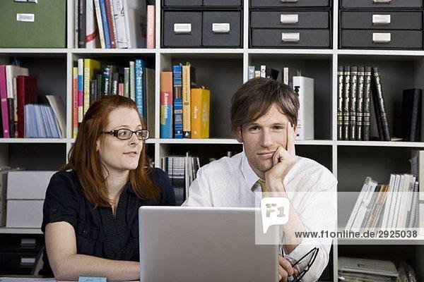 Eine Geschäftsfrau und ein Geschäftsmann  die mit einem Laptop arbeiten.
