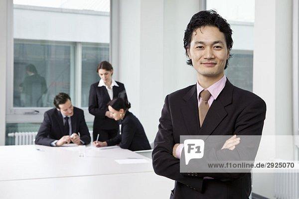 Porträt eines Geschäftsmannes in einem Vorstandszimmer mit unscharfen Geschäftsleuten im Hintergrund
