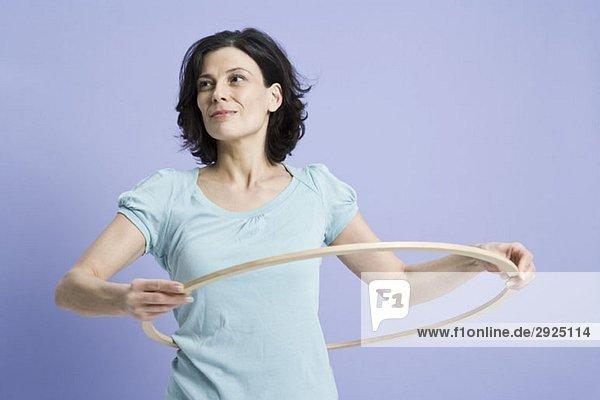 Eine Frau  die einen Hula-Reifen benutzt.