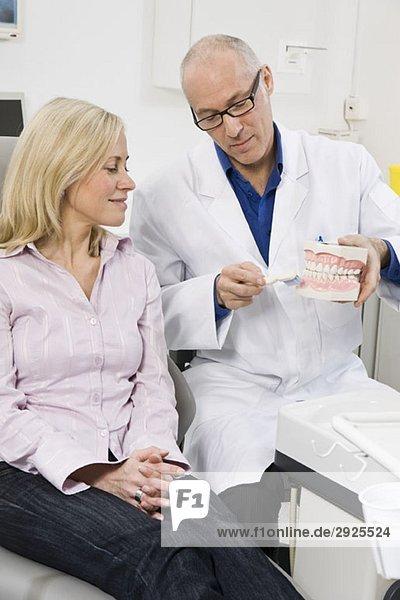 Ein Zahnarzt  der einem Patienten demonstriert.