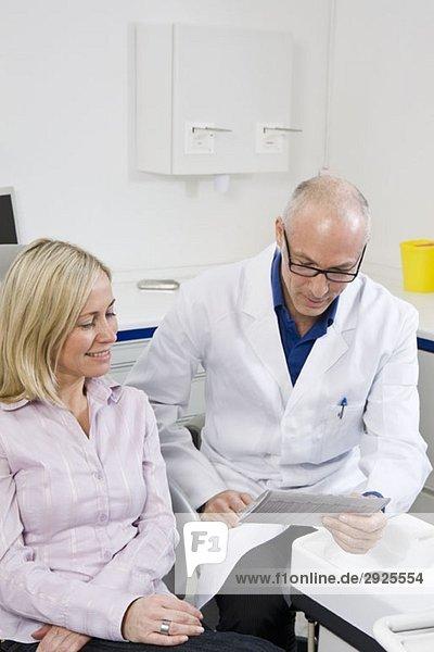 Ein Zahnarzt im Gespräch mit einem Patienten  der auf einem Zahnarztstuhl sitzt.