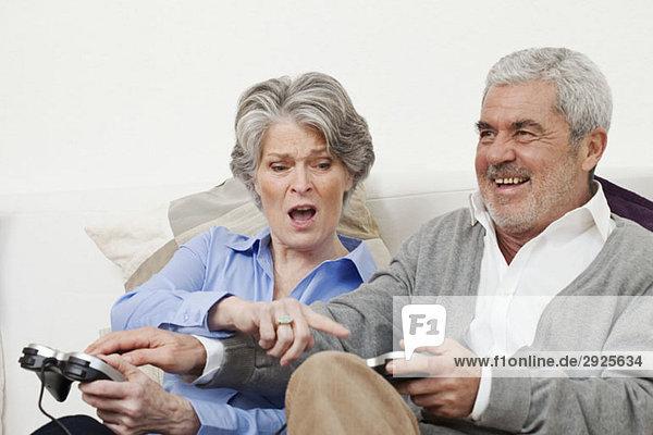 Ein älterer Mann und eine ältere Frau spielen ein Videospiel.