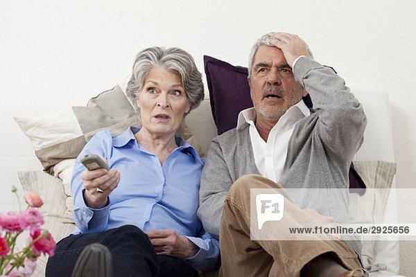 Ein Paar  das etwas Unglaubliches im Fernsehen sieht.