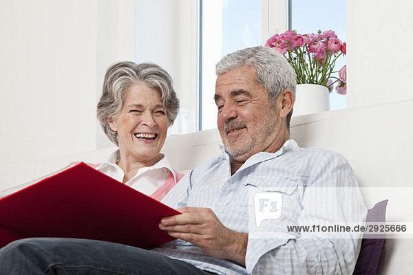Ein älteres Paar  das zusammen durch ein Buch schaut.