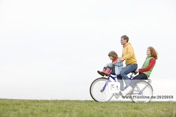 A young family riding on a bike together