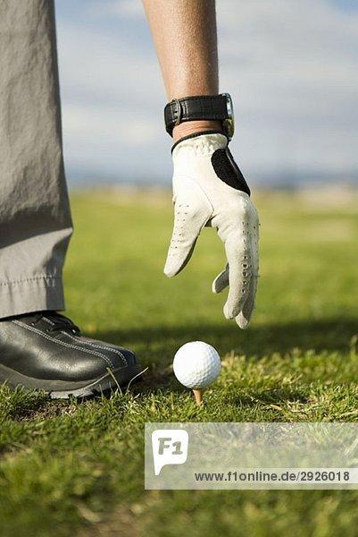 Detail einer Frau,  die einen Golfball auf ein Tee legt.
