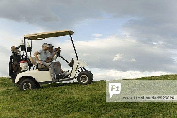Zwei Golfer  die in einem Golfwagen sitzen und lachen.