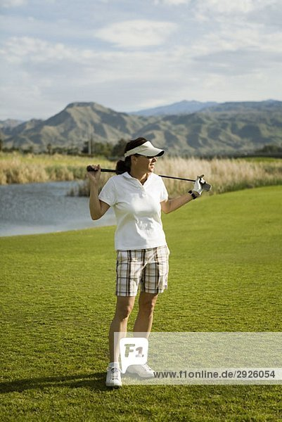 A golfer standing with golf clubs across her shoulders  Palm Springs  California  USA
