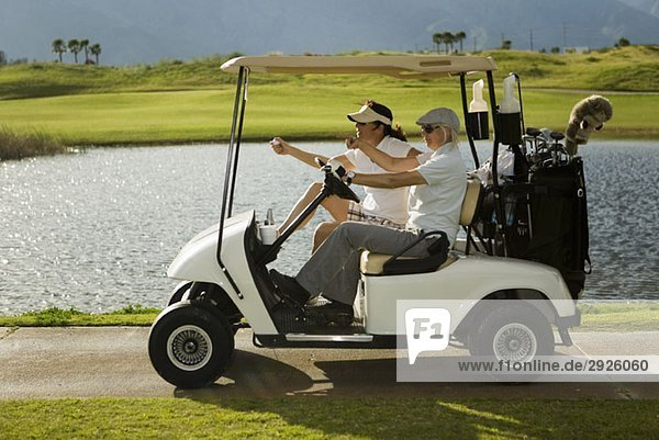 Zwei Golfer im Golfwagen