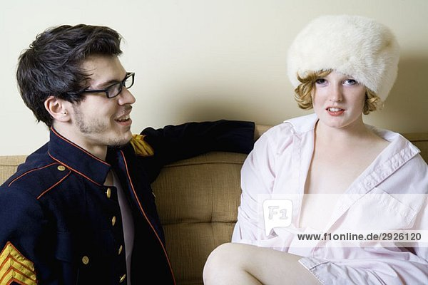 A young couple sitting on a sofa in costume