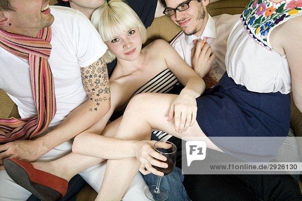 Eine Gruppe von Freunden  die zusammen auf einem Sofa gestapelt sind.