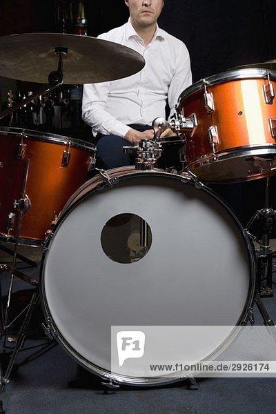A man sitting at a drum kit