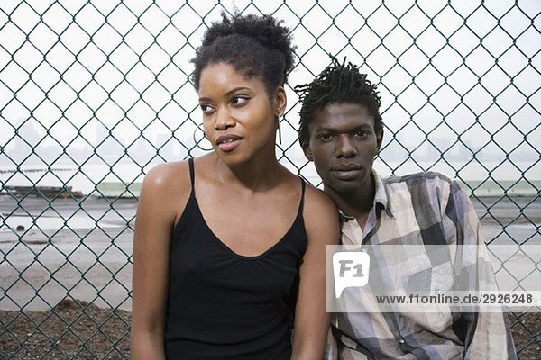 Ein junges Paar vor einem Kettengliederzaun