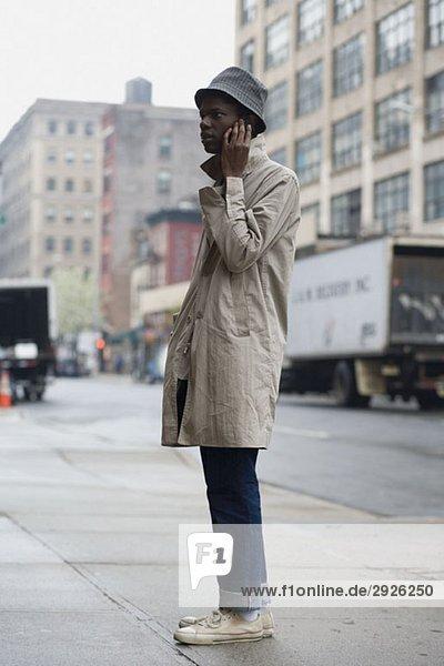Ein junger Mann  der auf einem Bürgersteig steht und ein Handy benutzt.