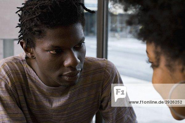 Ein junges Paar sitzend von Angesicht zu Angesicht