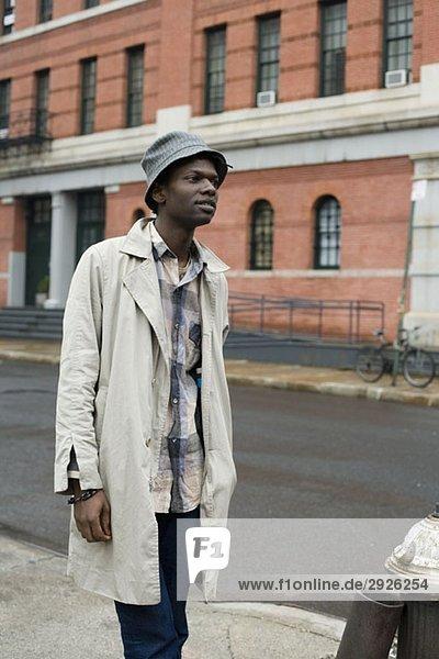 Ein junger Mann  der auf dem Bürgersteig steht.
