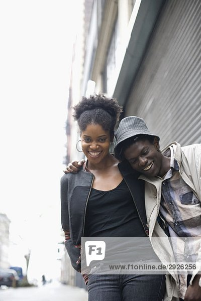 Ein junges Paar  das zusammen eine Straße entlang geht.