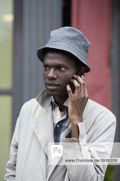 Ein junger Mann  der ein Handy benutzt.