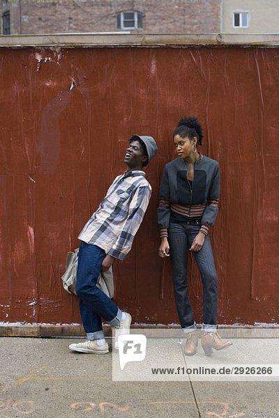 Ein junges Paar  das auf einem Bürgersteig steht.