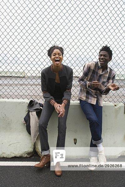 Ein junges Paar steht vor einem Kettengliedzaun